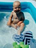 Ma?y dziecko siedzi w basenie i u?miechy, sztuki s?o?ce b?yszcz? lato zdjęcie royalty free