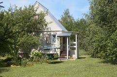 Mały lata dom na wsi w cieniu ogrodowi drzewa Zdjęcie Stock