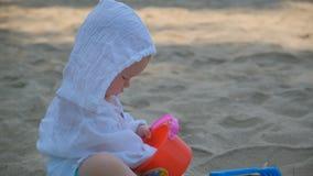 Ma?y ?liczny szcz??liwy dziecko bawi? si? z piaskiem i na pla?y zbiory