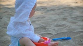 Ma?y ?liczny szcz??liwy dziecko bawi? si? z piaskiem i na pla?y zdjęcie wideo