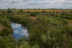 Mały rzeczny bieg przez poly i odbicia chmury w wodzie Fotografia Stock