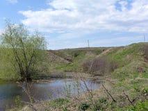 Mały staw w nizinie bezdrzewni wzgórza Zdjęcie Stock