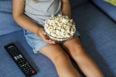 ma?y telewizor dziewczyny patrz? Szcz??liwa ?liczna ma?a dziewczynka trzyma puchar z popkornem zdjęcia royalty free