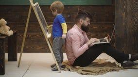 Ma?y ucze? z u?miechni?tym nauczycielem w sali lekcyjnej Bocznego widoku uroczy ma?e dziecko pisze na chalkboard Ch?odno facet w  zdjęcie wideo