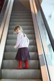 Małych dziewczynek spojrzenia z powrotem na eskalatorze Obrazy Royalty Free