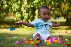 Mała amerykanin afrykańskiego pochodzenia chłopiec bawić się w trawie Fotografia Royalty Free