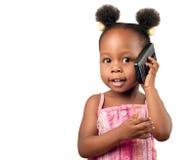 Mała amerykanin afrykańskiego pochodzenia dziewczyna opowiada telefon Fotografia Royalty Free