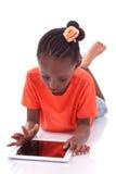 Mała amerykanin afrykańskiego pochodzenia dziewczyna używa pastylka komputer osobistego Zdjęcia Stock