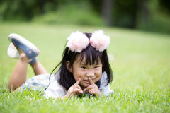 Mała azjatykcia dziewczyna bawić się na zielonej trawie przy parkiem Obraz Royalty Free