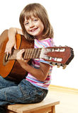 Mała dziewczynka bawić się klasyczną gitarę Obrazy Royalty Free