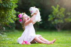 Mała dziewczynka bawić się z istnym królikiem Zdjęcia Royalty Free