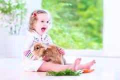 Mała dziewczynka bawić się z królikiem Fotografia Royalty Free