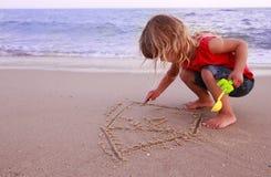 Mała dziewczynka rysuje dom morzem Zdjęcia Royalty Free