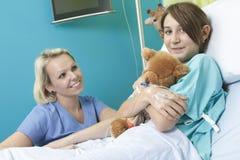 Mała dziewczynka w łóżku szpitalnym z pielęgniarką Obraz Royalty Free