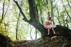 Mała dziewczynka w sukni z lalą siedzi na drzewie w lesie Obrazy Stock