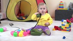 Mała kędzierzawa z włosami blondynki dziewczyna, opowiadający na starym zielonym telefonie, dzwoni mamy zbiory wideo