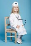 Mała śmieszna dziewczyna bawić się pielęgniarki Zdjęcie Stock