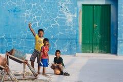 MAAFUSHI, МАЛЬДИВЫ - 5-ОЕ ЯНВАРЯ 2013: 3 босоногих мальдивских дет в красочных футболках привлекают внимание фотографа Стоковые Изображения