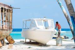 MAAFUSHI MALDIVERNA - JANUARI 5: Hantverkaren reparerar en snabb motorbåt för att vara klar för en ny turist- säsong Arkivfoton