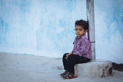 MAAFUSHI, MALDIVES - JANUARY 5, 2013: Small Maldivian boy with a deep serious eyes posing near a blue wall Royalty Free Stock Images