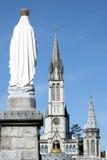 Maagdelijke Mary en basiliek in pelgrimsstad Lourdes Stock Fotografie