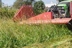 Maai gras met tractor en maaimachine stock afbeeldingen