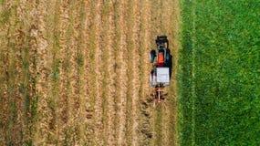 Maaidorser - de luchtmening, hommelmening van modern combineert tractor op het gouden hooigebied in de zomer Roterende harken met stock fotografie