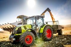 Maaidorser en tractor met aanhangwagen het leegmaken oogstlandbouwer het werk details De machines van de landbouwindustrie royalty-vrije stock fotografie