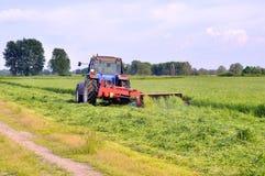 Maaiend gras met een tractor stock afbeeldingen
