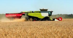 Maaimachine op het gebied tijdens de oogst en achter hem passenmaaimachine Prores, langzame motie stock video