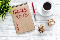 Maak een doelstellingen lijst voor 2018 Notitieboekje dichtbij pen en kop van koffie op grijze houten hoogste mening als achtergr Stock Foto's