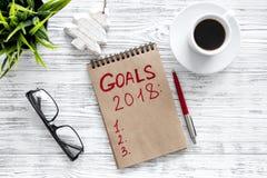 Maak een doelstellingen lijst voor 2018 Notitieboekje dichtbij pen, glas en kop van koffie op grijze houten hoogste mening als ac Stock Fotografie