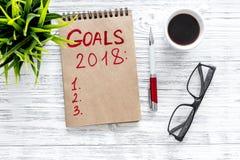 Maak een doelstellingen lijst voor 2018 Notitieboekje dichtbij pen, glazen en kop van koffie op grijze houten hoogste mening als  Royalty-vrije Stock Fotografie