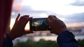 Maak een foto op de telefoon van een mooie zonsondergang in de stad dichtbij de rivier, close-up langzame motie, 1920x1080, volle stock video