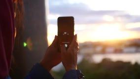 Maak een foto op de telefoon van een mooie zonsondergang in de stad dichtbij de rivier langzame motie, 1920x1080, volledige hd stock videobeelden