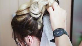Maak een sluier aan het haar van de bruid vast stock videobeelden