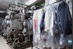 Maak ingepakte kleren schoon die in chemisch reinigen hangen Stock Foto