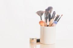 Maak omhoog borstels in houder en schoonheidsmiddelen op wit Royalty-vrije Stock Foto's