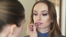 Maak omhoog de contour van de kunstenaarstekening op meisjes` s lippen 4K stock video