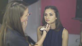 Maak omhoog kunstenaar die een stemmende room toepassen op een models-gezicht in een studio stock footage