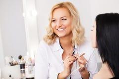 Maak omhoog kunstenaar die gezichtspoeder toepassen op een klant in een schoonheidsopslag stock fotografie