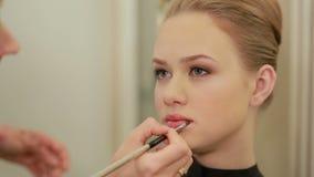 Maak omhoog kunstenaar die lippenstift met borstel op vrij schitterende vrouwenlippen toepassen Close-up van visagiste en jong me stock video