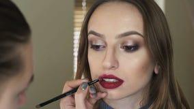 Maak omhoog kunstenaar die lippenstift op meisjes` s lippen 4K toepassen stock footage