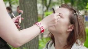 Maak omhoog kunstenaar toepast stichting op meisjes` s gezicht vóór photoshoot stock videobeelden