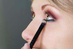 Maak omhoog kunstenaar werkend in studio omhoog maken, toepassend make-up royalty-vrije stock fotografie