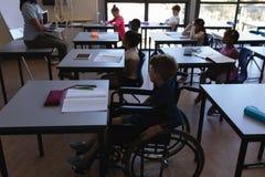 Maak schooljongen met klasgenoten onbruikbaar die en bij bureau in klaslokaal bestuderen zitten stock foto