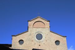 Maak spruit van de voorgevel van de metselwerkkerk met blauwe open hemel in San Gimignano schoon royalty-vrije stock afbeeldingen