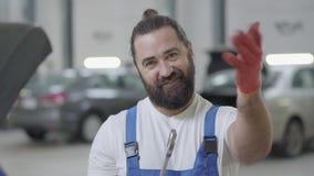 Maakt de portret succesvolle professionele werktuigkundige het uitnodigen gebaren en glimlacht holding reusachtige moersleutel in stock videobeelden