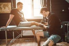Maakt de tatoegerings mannelijke kunstenaar een tatoegering op een vrouwelijk been stock afbeeldingen