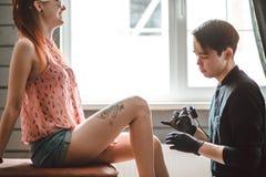 Maakt de tatoegerings mannelijke kunstenaar een tatoegering op een vrouwelijk been royalty-vrije stock afbeeldingen